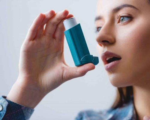 close-up-view-of-young-woman-with-asthma-using-inh-DYEHUDX_11zon